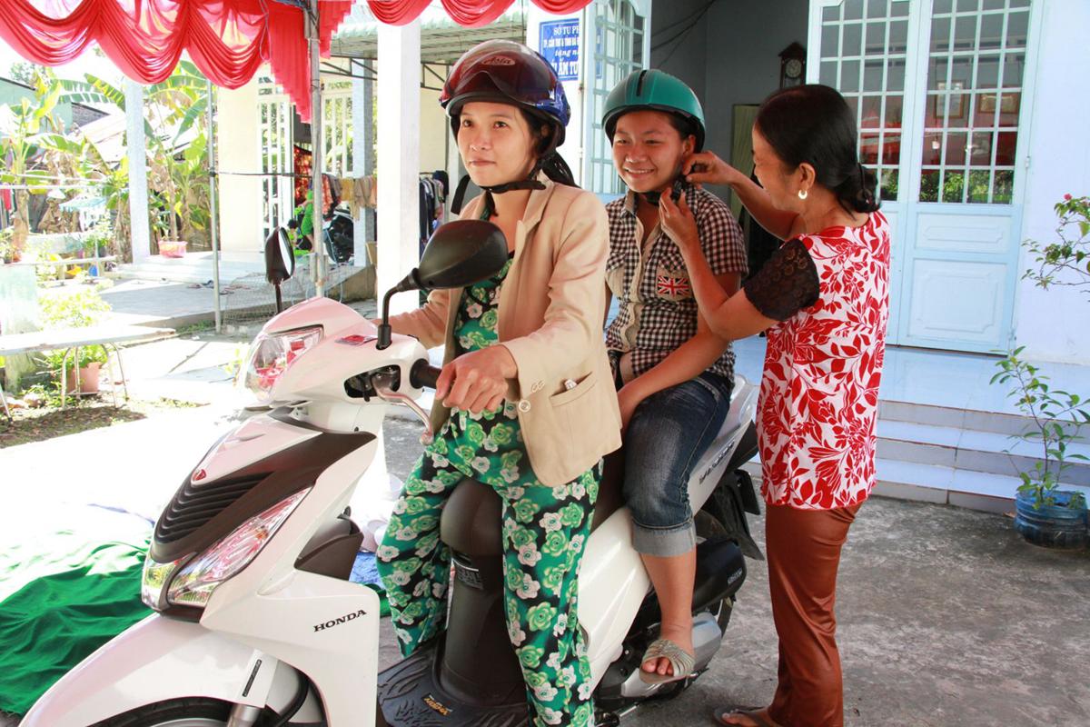 """Hội viên phụ nữ tham gia CLB """"Phụ nữ với ATGT"""" nghiêm chỉnh chấp hành việc đội mũ bảo hiểm khi tham gia giao thông."""