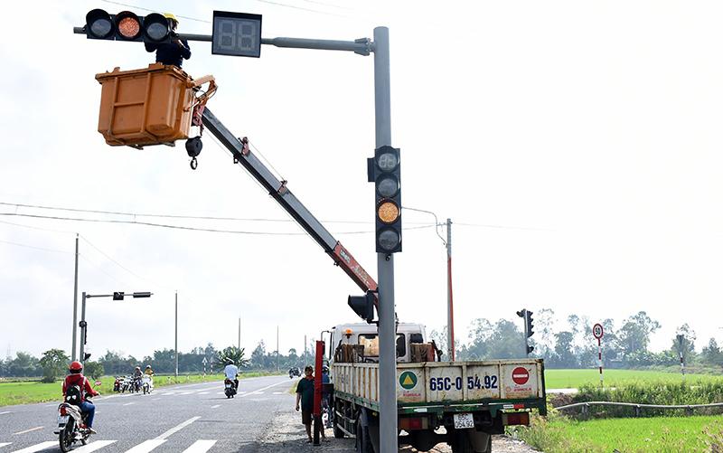 Công nhân đang lắp hệ thống đèn tín hiệu giao thông tại giao lộ tuyến tránh nội thị Thốt Nốt với đường Nguyễn Trọng Quyền. Ảnh: XUÂN ĐÀO