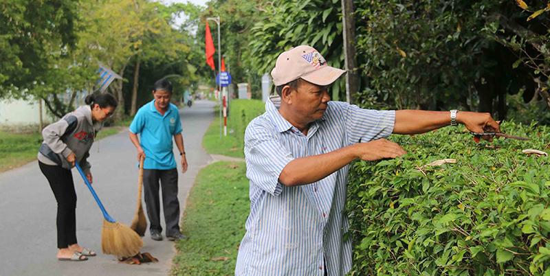 Người dân làm vệ sinh, cắt tỉa hàng rào cây xanh trên tuyến đường Đinh Công Chánh (phường Long Tuyền). Ảnh: ĐĂNG HUỲNH