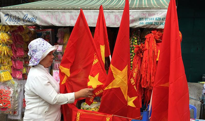 Rất nhiều khách hàng đã mua Quốc kỳ Việt Nam trước trận thi đấu. Ảnh: NAM HƯƠNG
