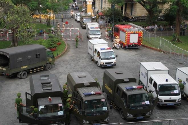 Lực lượng chức năng dẫn giải các bị cáo trong vụ án đặt bom xăng tại Sân bay Tân Sơn Nhất, ngày 27/12/2017. Ảnh: THÀNH TRUNG/TTXVN