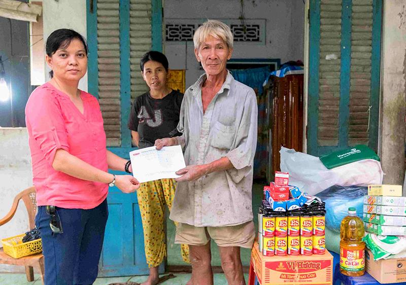 Chị Tuyết Lan trao quà và tiền mặt cho ông Hùng. Ảnh: X.ĐÀO