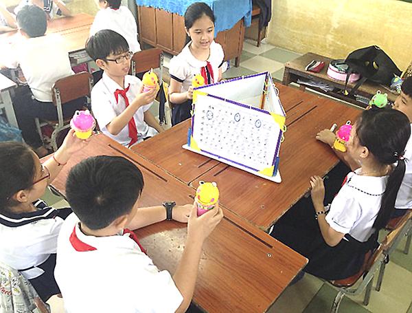 Học sinh tập gõ nhịp trong giờ học nhạc với chiếc hộp đa năng. Ảnh: Minh Trang (giáo viên Trường Tiểu học Bình Thủy).