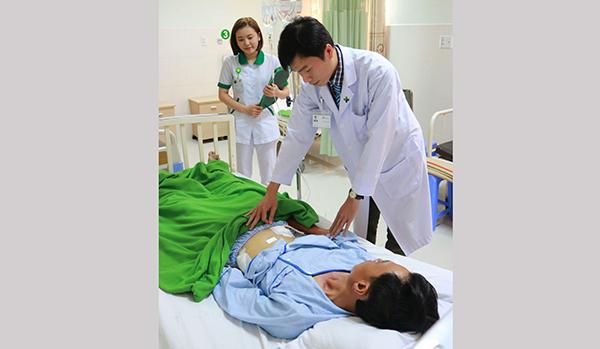 Bác sĩ Huỳnh Huy Cường thăm khám cho bệnh nhân sau phẫu thuật.