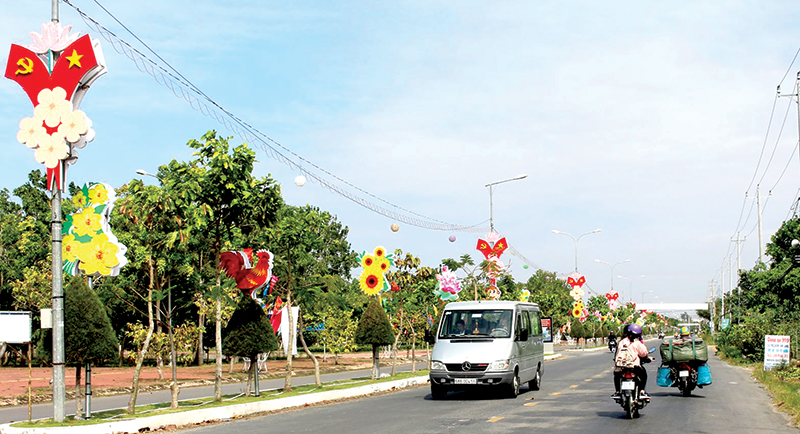Cây xanh trên vỉa hè, con lươn tỉnh lộ 919 (thuộc địa bàn huyện Vĩnh Thạnh) phát triển tốt, trang trí đèn hoa tạo môi trường xanh, sạch, đẹp ở nông thôn. Ảnh: HÀ VĂN