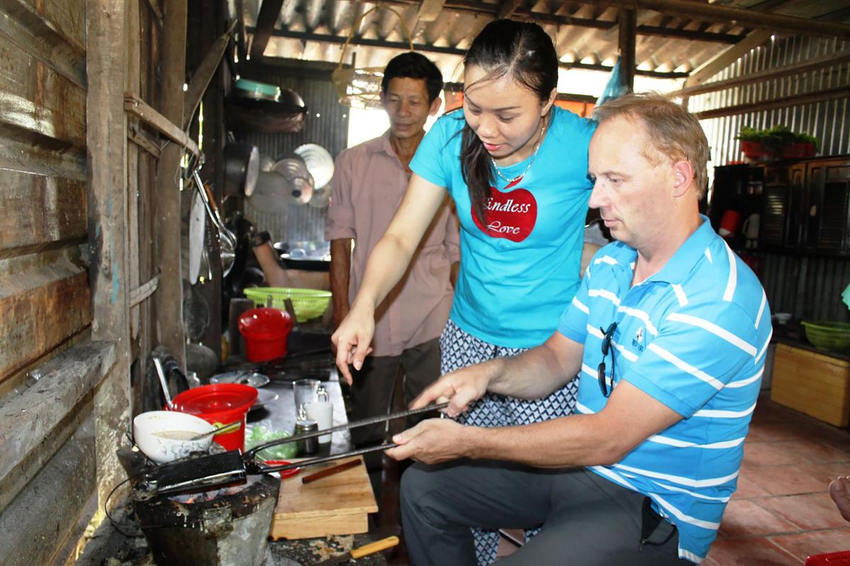Du khách nước ngoài trải nghiệm làm bánh kẹp tại khu du lịch Cồn Sơn, quận Bình Thủy. Ảnh: Lệ Thu