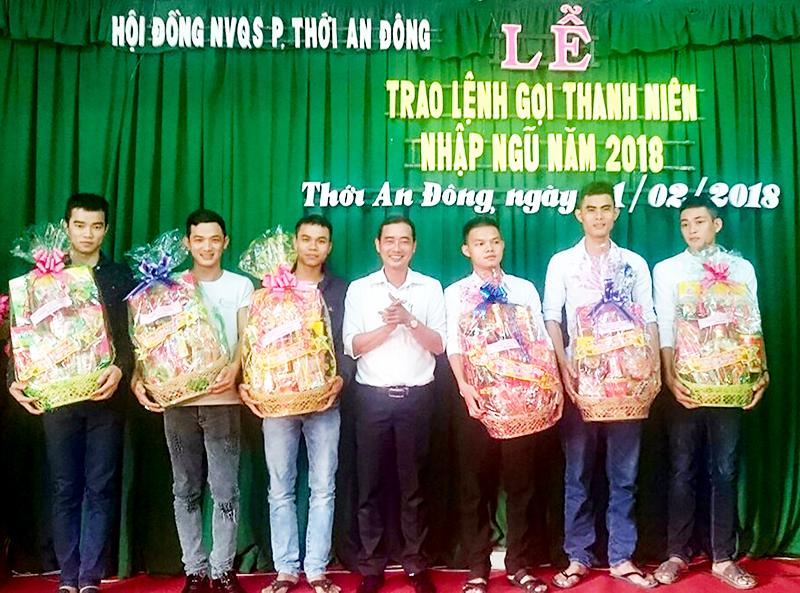 Đồng chí Hà Quốc Hữu, Chủ tịch UBND phường Thới An Đông tặng quà Tết cho thanh niên trúng tuyển năm 2018. Ảnh: C.T.V.