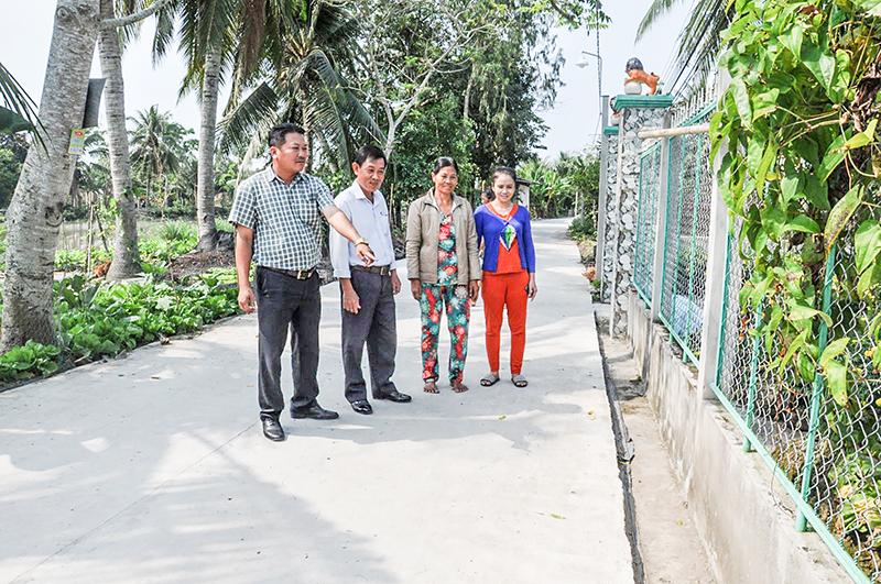 Đồng chí Hồ Việt Thống, Bí thư Chi bộ ấp Trường Trung (bìa trái) đã vận động nhân dân đóng góp cùng nhà nước tráng bê tông, mở rộng tuyến đường từ chợ Ba Mít đến cầu Cây Dầu. Ảnh: ANH DŨNG