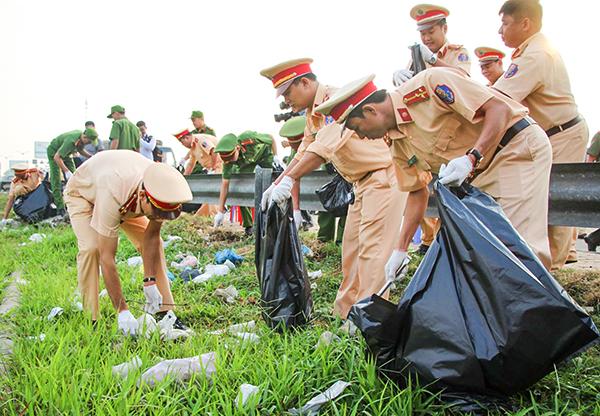 Cảnh sát giao thông TP Cần Thơ phối hợp dọn rác, vừa làm đẹp mỹ quan đô thị, vừa đảm bảo an toàn giao thông các phương tiện. Ảnh: KIỀU CHINH
