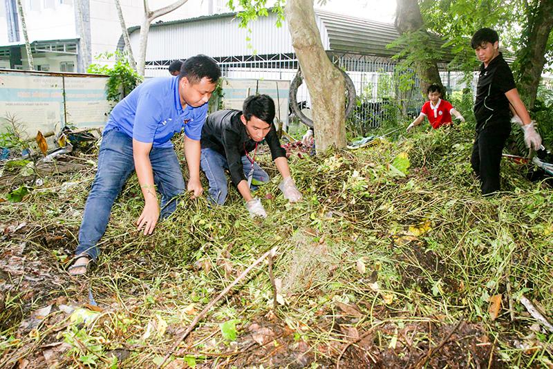 Thành viên CLB Môi trường dọn vệ sinh khuôn viên phía sau Văn phòng Đoàn Trường Đại học Cần Thơ. Ảnh: Q. THÁI