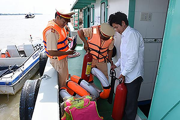 Cảnh sát đường thủy Trạm Thới An thuộc Phòng PC68 đang kiểm tra về quy định của Luật Giao thông ĐTNĐ đối với người điều khiển phương tiện thủy tuyến sông Hậu. Ảnh: XUÂN ĐÀO