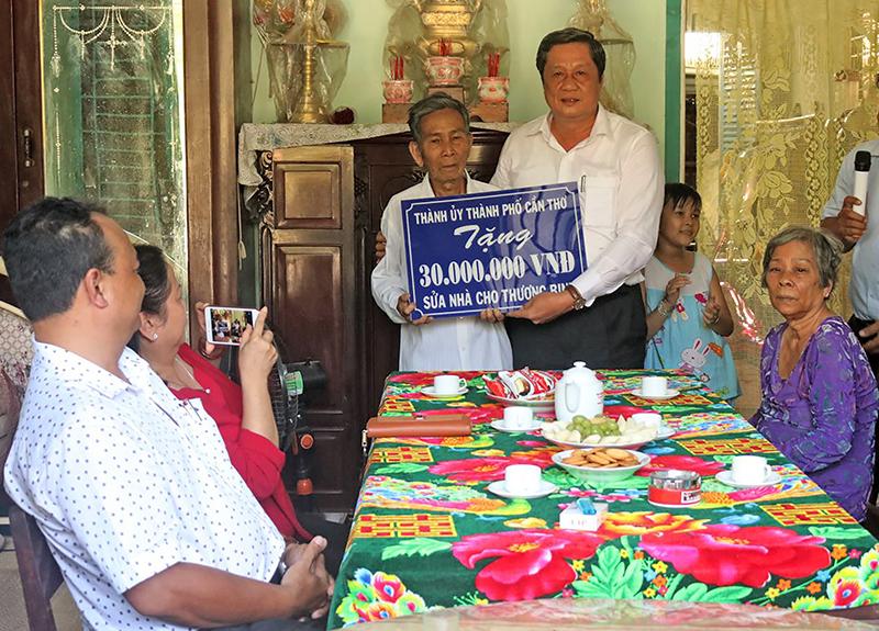 Đồng chí Phạm Văn Hiểu, Phó Bí thư Thường trực Thành ủy, Chủ tịch HĐND TP Cần Thơ trao bảng tượng trưng số tiền sửa chữa nhà cho gia đình ông Phạt. Ảnh: CHẤN HƯNG