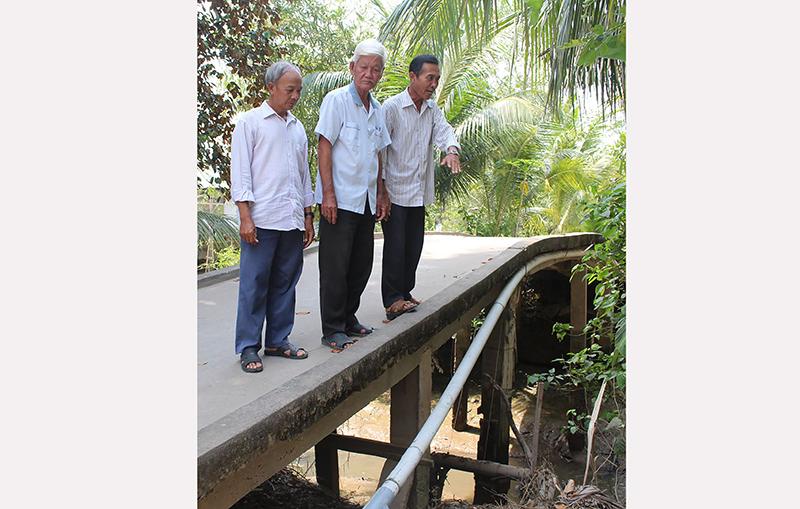 Ông Nguyễn Văn Tám (giữa) cùng với cán bộ ấp lên kế hoạch mở rộng cầu Cái Tắc 4m để phục vụ giao thương thuận lợi.