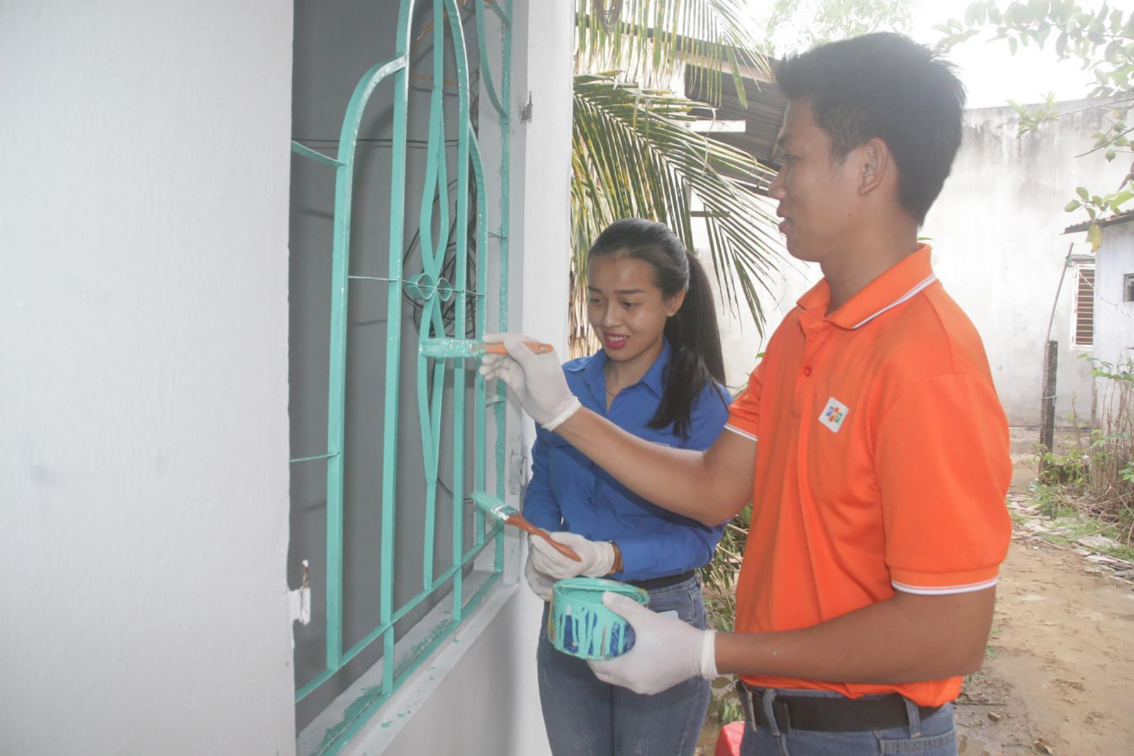 Tuổi trẻ quận Cái Răng và nhân viên Chi nhánh Công ty TNHH phân phối FPT tại Mekong sơn sửa nhà cho chị Sứt ở khu vực 3, phường Hưng Thạnh. Ảnh: QUỐC THÁI