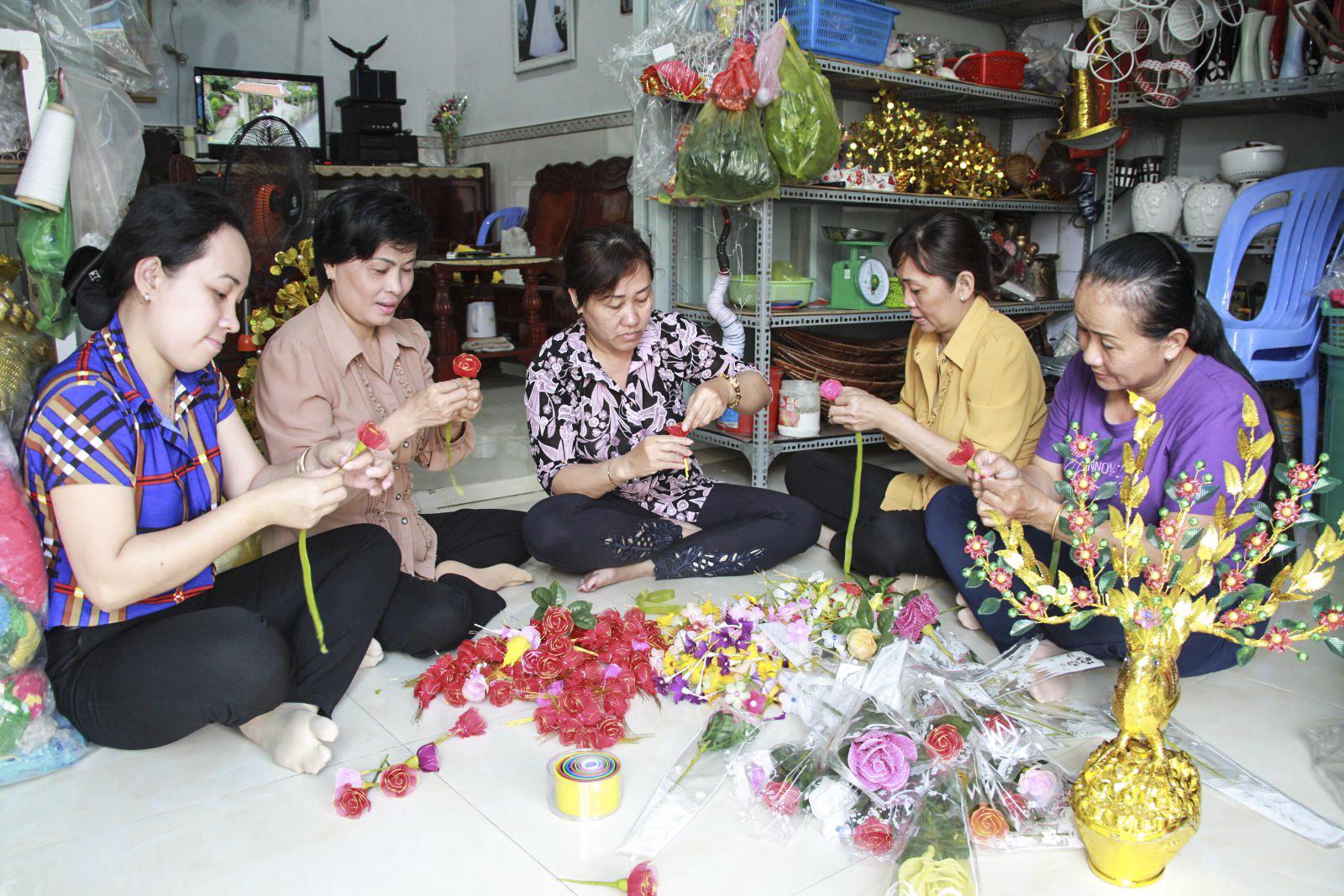 Nghề làm hoa voan giúp chị Thảo (ngồi giữa), phường Bùi Hữu Nghĩa, quận Bình Thủy phát triển kinh tế gia đình bền vững. Ảnh: HỒNG VÂN