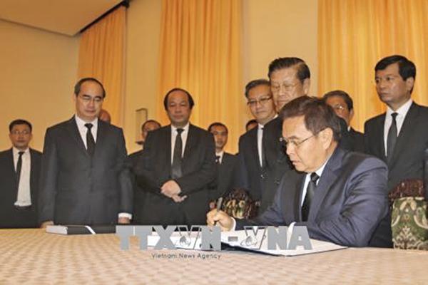 Chủ tịch Mặt trận Lào xây dựng đất nước Xay - xỏm - phôn Phôm - vi - hản viếng và ghi sổ tang nguyên Thủ tướng Chính phủ Phan Văn Khải. Ảnh: Thanh Vũ - TTXVN