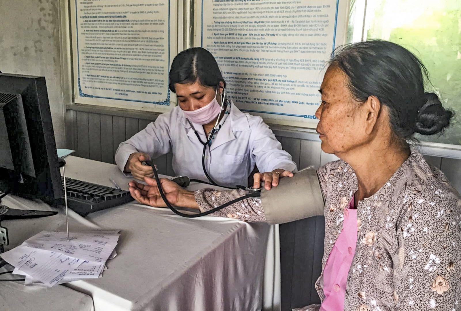 Bác sĩ Hoàng Thị Thu Hà khám bệnh tăng huyết áp cho người dân tại trạm y tế. Ảnh: H.HOA