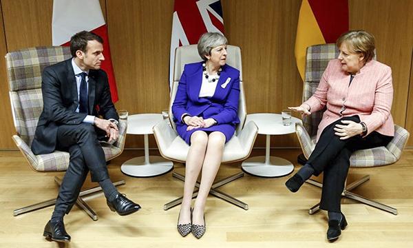 Thủ tướng Anh Theresa May (giữa) trong cuộc gặp Tổng thống Pháp Emmanuel Macron và Thủ tướng Đức Angela Merkel bên lề hội nghị hôm 22-3. Ảnh: BBC