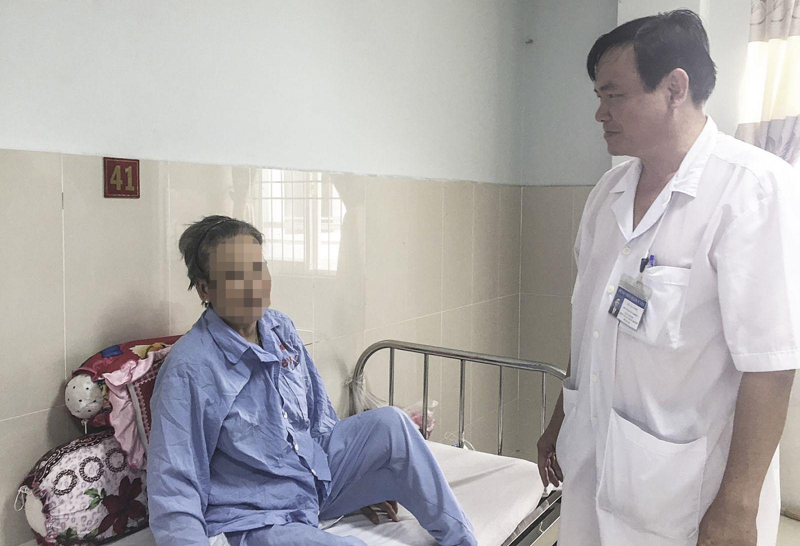 Bác sĩ Lê Văn Công thăm hỏi bệnh nhân Mỹ V. sau phẫu thuật thay đốt sống. Ảnh: H.HOA