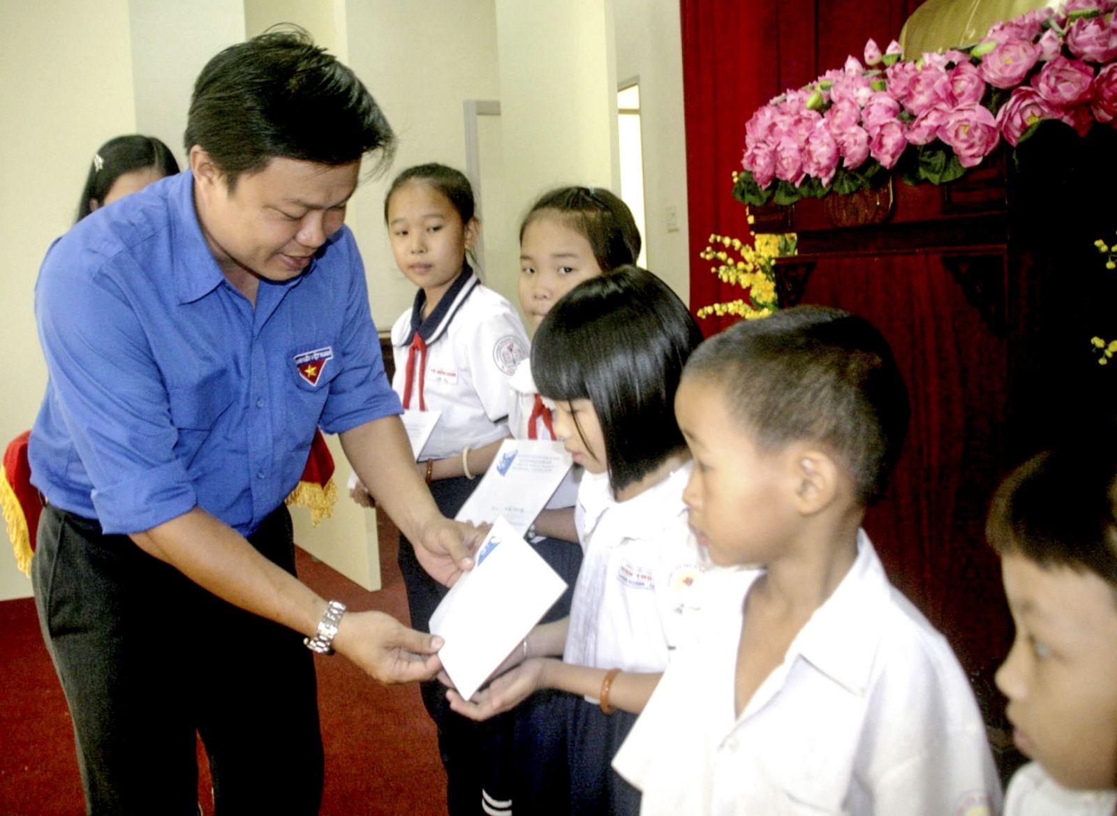 Anh Huỳnh Thái Nguyên, Phó Bí thư Thường trực Thành đoàn Cần Thơ trao học bổng cho học sinh có hoàn cảnh khó khăn trên địa bàn quận Bình Thủy. Ảnh: Q. THÁI