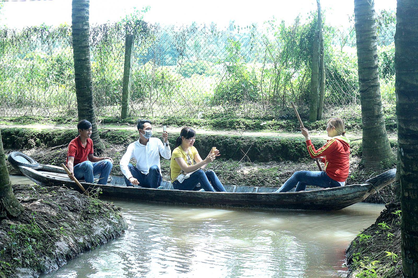 Du khách trải nghiệm bơi ghe ở vườn dừa của ông Lê Tấn Nhường. Ảnh: ÁI LAM