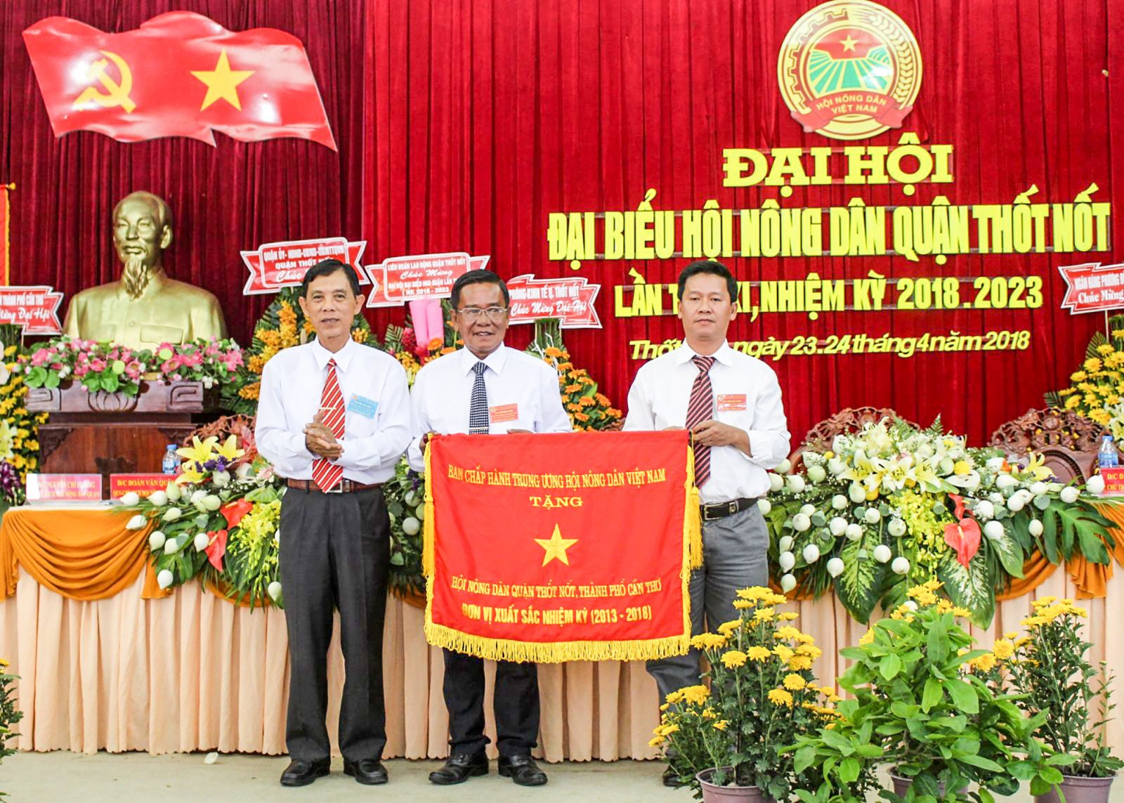 Ông Lê Bá Phước, Chủ tịch HND thành phố (bìa trái) trao cờ của Trung ương HND Việt Nam cho lãnh đạo HND quận Thốt Nốt. Ảnh: THANH THƯ