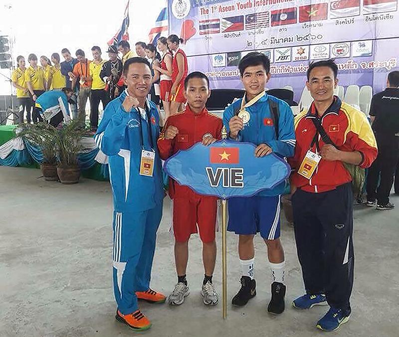 Võ sĩ Đỗ Hồng Ngọc (thứ hai từ phải qua) cùng Ban Huấn luyện sau khi đoạt HCV tại Thái Lan. Ảnh: ANH TUẤN