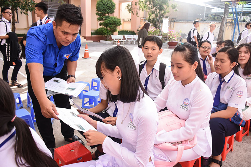 Đoàn viên phát tờ rơi tuyên truyền ATGT trong học sinh. Ảnh: XUÂN ĐÀO