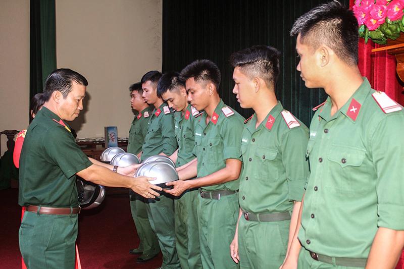 Đại tá Trịnh Hoài Văn, Phó Chỉ huy trưởng Bộ CHQS thành phố trao nón bảo hiểm cho cán bộ, chiến sĩ. Ảnh: PHẠM TRUNG