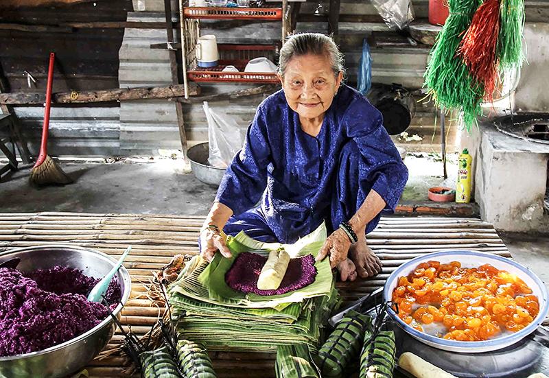 Nghệ nhân Huỳnh Thị Trọng gói bánh tét lá cẩm. Ảnh: ĐĂNG HUỲNH