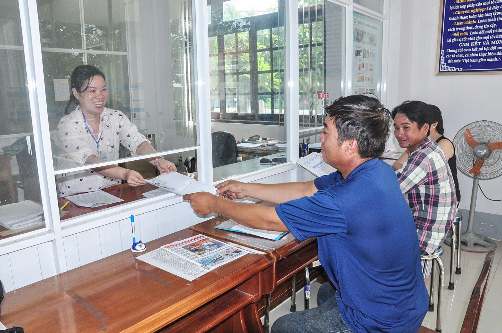 Công chức bộ phận một cửa Chi cục Thuế huyện niềm nở, nhiệt tình phục vụ người nộp thuế. Ảnh: ANH DŨNG