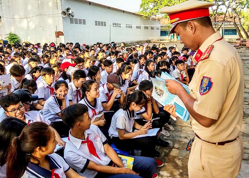 Cảnh sát giao thông Công an huyện Phong Điền phát tờ rơi tuyên truyền Luật Giao thông đường bộ và đường thủy nội địa cho học sinh trên địa bàn huyện. Ảnh: XUÂN ĐÀO