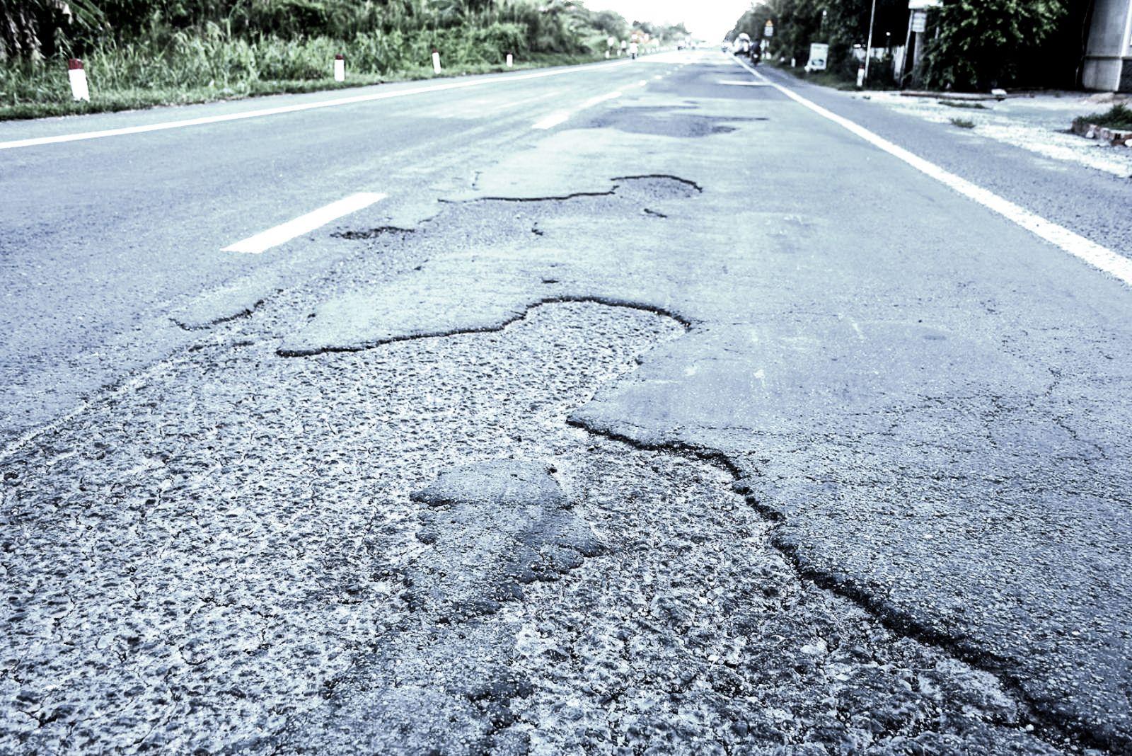 Mặt đường quốc lộ 61C đoạn gần khu vực cầu Rạch Sung, xã Nhơn Nghĩa, huyện Phong Điền bị bong tróc rất nhiều, gây nguy hiểm cho các phương tiện lưu thông. Ảnh: XUÂN ĐÀO