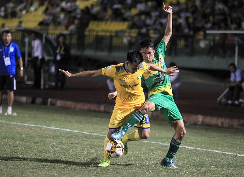Hữu Dũng (phải) tranh chấp bóng với cầu thủ Sông Lam Nghệ An trong trận đấu trên sân Cần Thơ. Ảnh: NGUYỄN MINH