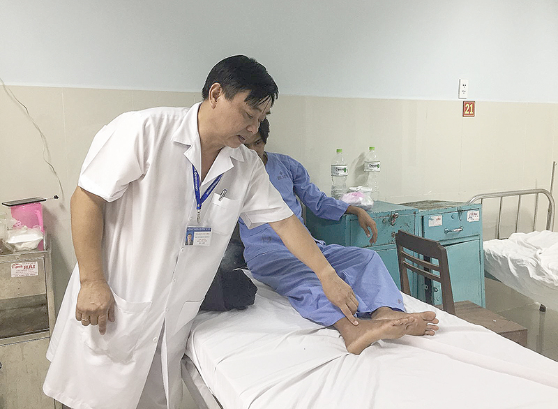 Đại tá Nguyễn Văn Vinh, Chủ nhiệm Khoa Nội tiêu hóa và Bệnh máu, BV Quân Y 121, xem vết rắn cắn trên chân bệnh nhân. Ảnh: H.HOA