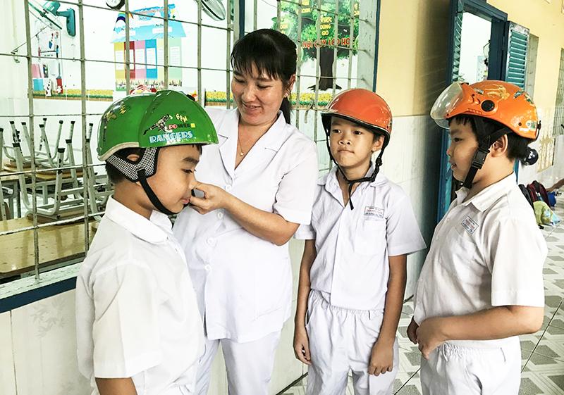 Cô Lê Thị Phương Uyên, bảo mẫu lớp 2A1, Trường Tiểu học Trần Quốc Toản, thường xuyên nhắc nhở học sinh đội MBH khi tham gia giao thông để đảm bảo an toàn. Ảnh: KIỀU CHINH