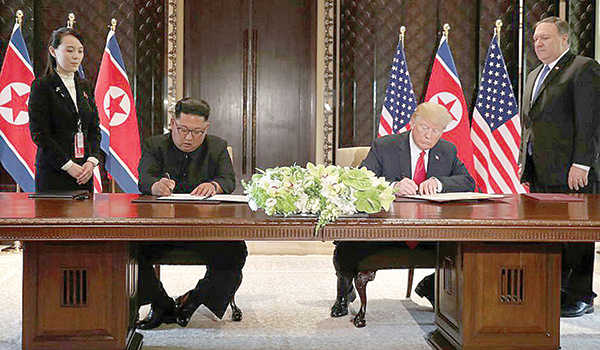 Tổng thống Mỹ Donald Trump (phải) và lãnh đạo Triều Tiên Kim Jong-un ký Tuyên bố chung ngày 12-6. Ảnh: Reuters