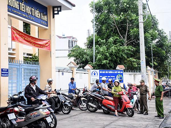 Công an phường Xuân Khánh và lực lượng Bảo vệ dân phố phường nhắc nhở các hộ mua bán không lấn chiếm vỉa hè khu vực trước cổng Trường Tiểu học Tô Hiến Thành. Ảnh: XUÂN ĐÀO