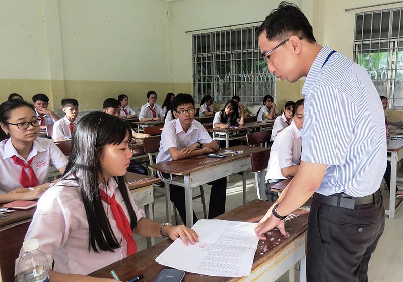 Cán bộ coi thi hướng dẫn thủ tục thi cho thí sinh dự thi tuyển lớp 10 tại điểm thi Trường THCS Lương Thế Vinh. Ảnh: B.NGỌC