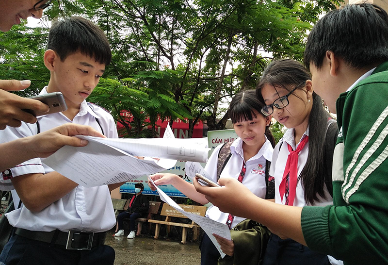 Thí sinh trao đổi bài thi sau giờ thi môn tiếng Anh, tại điểm thi Trường THPT Nguyễn Việt hồng. Ảnh: B.NGỌC