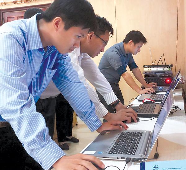 Các đại biểu tìm hiểu, trải nghiệm công cụ E-MAP trong tìm kiếm thông tin và xác định chính xác vị trí vùng nuôi cá tra. Ảnh: MỸ THANH