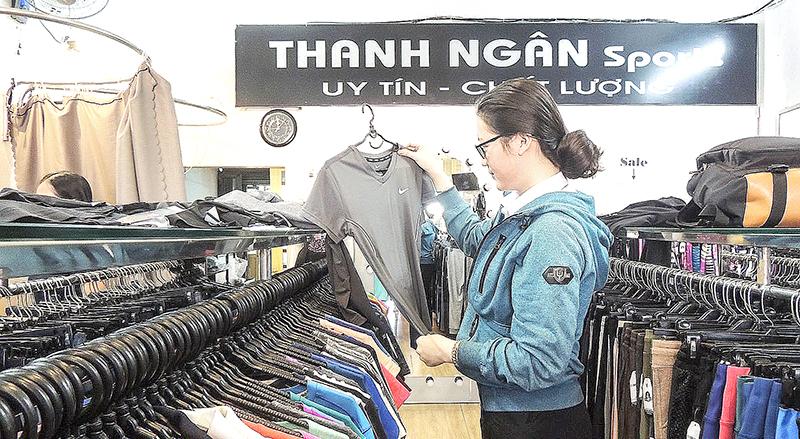 Khách hàng lựa chọn trang phục tại Cửa hàng Thanh Ngân Sports. Ảnh: CHI MAI