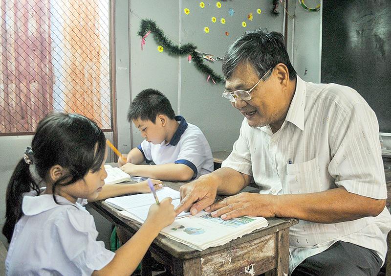 Ông Thời chỉ dẫn các em học sinh tại lớp học tình thương. Ảnh: BÌNH NGUYÊN