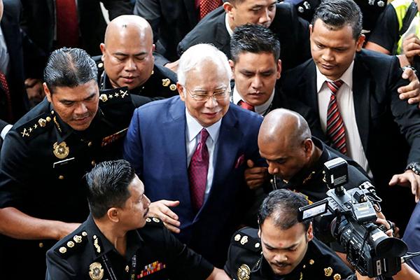 Ông Najib (giữa) đến tòa trong vòng vây lực lượng an ninh và giới truyền thông. Ảnh: Reuters