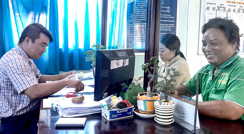Anh Phạm Thanh Bình, Công chức Tư pháp - Hộ tịch của UBND thị trấn Thới Lai đang tiếp nhận, giải quyết thủ tục hành chính cho người dân. Ảnh: CHẤN HƯNG