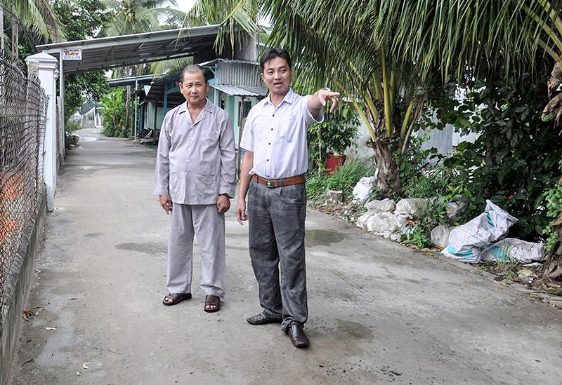 Đồng chí Nguyễn Hữu Trí, Bí thư Chi bộ, Trưởng khu vực Quy Thạnh 2 (bên phải) vận động nhân dân giữ gìn tuyến đường Bích Vàm – Cái Ngãi sạch đẹp. Ảnh: ANH DŨNG