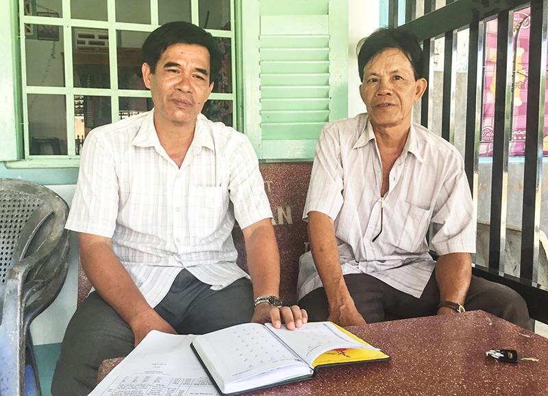 Ông Đỗ Hữu Tám, Trưởng khu vực Tràng Thọ B (bên trái), đang tuyên truyền, vận động người dân tham gia BHYT. Ảnh: CHẤN HƯNG