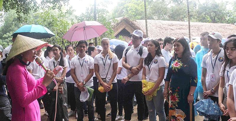Các bạn trẻ kiều bào đến từ 29 quốc gia và vùng lãnh thổ nghe giới thiệu tại Khu di tích Kim Liên, huyện Nam Đàn, tỉnh Nghệ An. Ảnh: NGUYỄN OANH - TTXVN