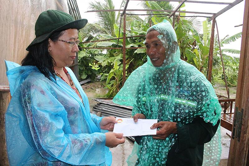 Bà Nguyễn Thúy Hằng, Phó Chủ tịch UBMTTQVN TP Cần Thơ (bên trái) hỗ trợ người dân bị sập nhà do lốc xoáy tại xã Đông Thuận, huyện Thới Lai. Ảnh: H.VĂN