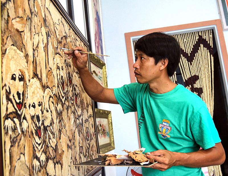 Anh Lê Hoàng Nhân sáng tác tranh bằng vật liệu vỏ tràm. Ảnh: PHƯƠNG ANH